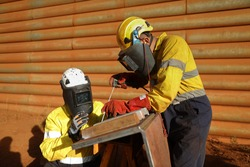 Safety workplace welder wearing dark safety shield mask eyes protection welding leather glove welding chute liners repairing while supervisor is guiding inspecting by his side Australia mining site