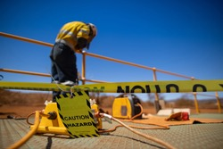 Safety workplace yellow striped caution tape warning sign barricade exclusion zone preventing from public access while defocused construction worker welder welding repairing fence