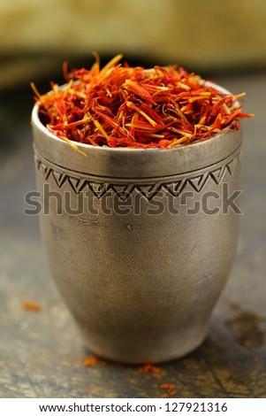 Saffron spice in metal bowl macro shot soft focus