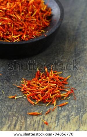 saffron treads in pile, on black wooden board