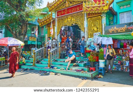 SAGAING, MYANMAR - FEBRUARY 21, 2018: The crowded entrance to Soon Oo Ponya Shin Pagoda (Summit Pagoda), people leave their footwear on the steps and go to the Shrine, on February 21 in Sagaing #1242355291