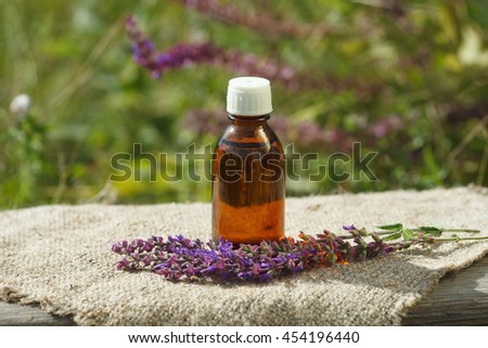 sage oil container with blooming sage background