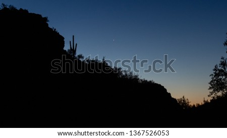 Saguaro National Park West just off of Picture Rocks road near dawn with the Sonoran Desert sky lighting up and a mountain with cactus in silhouette and a star visible. Pima County, Tucson, Arizona.