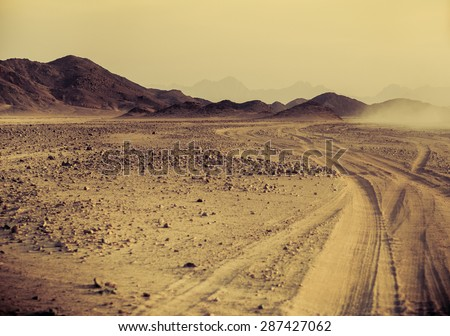 Sahara desert at sunset - mountain landscape with dust off road and stone hills on a horizon. Exotic adventure and expedition in arid wilderness. Safari and extreme travel in Africa.
