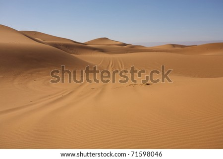 Sahara desert close to Merzouga in Morocco with blue sky and clouds - stock photo