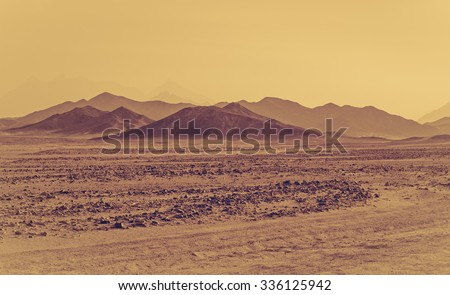 Sahara desert - mountain landscape and stone hills silhouettes on a horizon. Exotic adventure in Arabian desert, extreme travel to Egypt. Sandstorm in african desert. Extreme safari on off-road car.