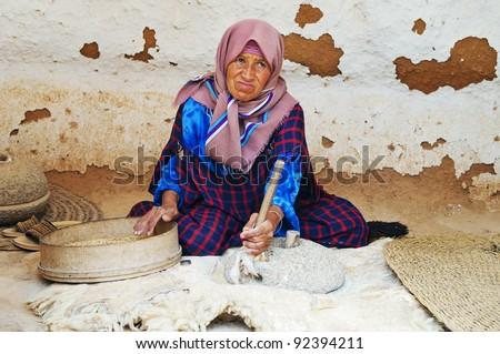 SAHARA DESERT, TUNISIA - AUGUST 30: Old woman grinds grains for flour on August 30, 2011 near Sahara Desert, Tunisia