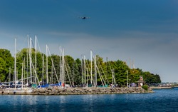 Saiboats at rest in a marina on the St. Lawrence River with a military transport airplane flyover though a blue sky.