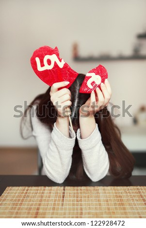 Said girl holding two parts of broken hart at home