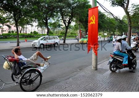 SAIGON - FEB 15: An unidentified rickshaw driver waits for tourists on the streets of Ho Chi Minh on Feb 15, 2013 in Saigon, Vietnam. In Saigon are more than 5 million motorbikes and rickshaws.