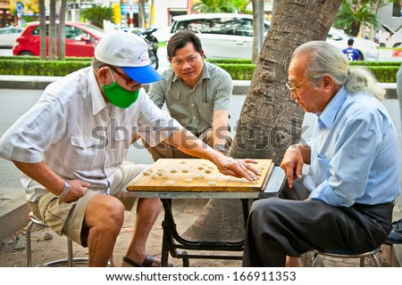 SAIGON, VIETNAM-NOVEMBER 17, 2013:Unidentified men playing board game  Xiangqi on November 17,2013 in Saigon, Vietnam.Board games have been played in most cultures and societies throughout history.