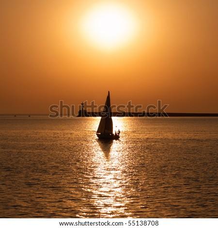 Sail boat against sea sunset. Colorful marine landscape.