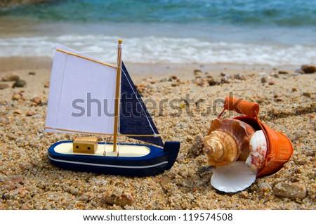 Sail boat and bucket shells at the beach