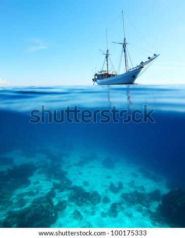 Sail boat in a tropical calm sea on a surface and coral reefs  underwater