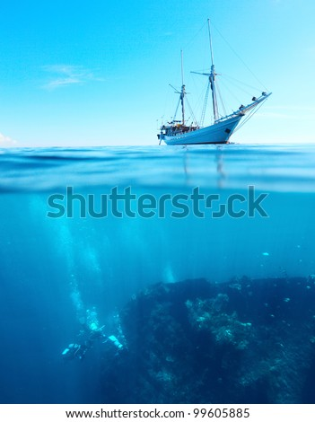 Sail boat in a tropical calm sea on a surface and divers underwater exploring a shipwreck