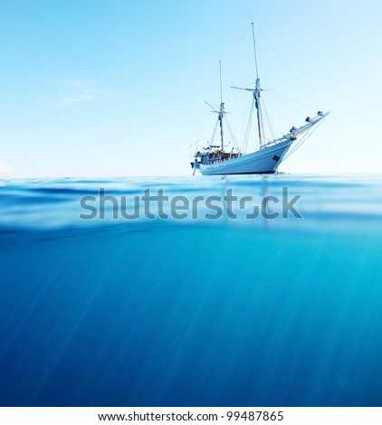 Sail boat in tropical calm sea on a surface and underwater sea view with sun beams
