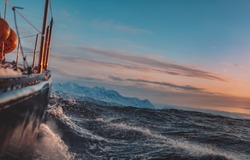 Sail boat on rough morning in Norway sea water with splashes, side view with snowy mountains on background