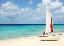 Sail boat on tropical beach with blue water background