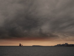Sail boat silhouette going into the port, Dramatic stormy sky, Galway bay and city, Ireland. Atlantic ocean.