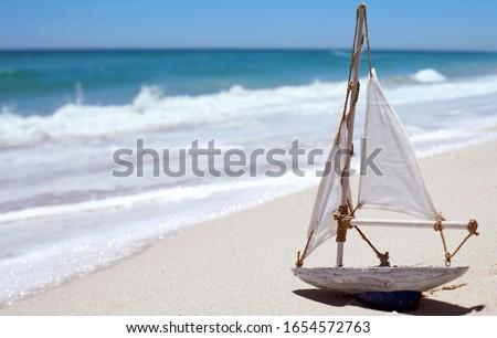 Sail boat toy on sandy beach