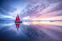 Sail boat with red sails cruising among ice bergs during sunrise. Disko Bay, Greenland.