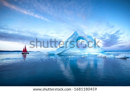 Sail boat with red sails cruising among massive ice bergs during dusk. Disko Bay, Greenland.