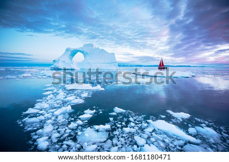 Sail boat with red sails cruising next to a pierced ice berg after sunset. Disko Bay, Greenland.