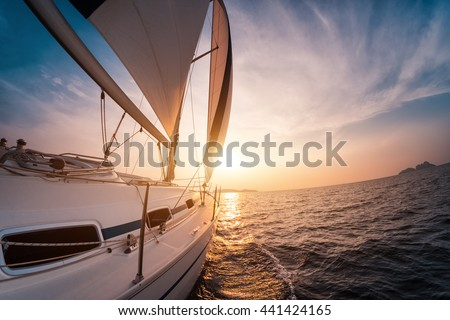 Sail boat with set up sails gliding in open sea at sunset