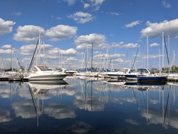 Sail boats and yachts parked at marina yacht club. Beautiful sunny day, bright white clouds, deep blue sky reflecting in still water. Luxury lifestyle, adventure, sail, travel concept. Ontario Canada.