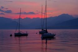 Sail boats moored on Lake Como, Italy, at sunset.