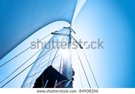 Sail over clear blue sky, sailboat over natural background with sunlight, summertime activities and extreme sport