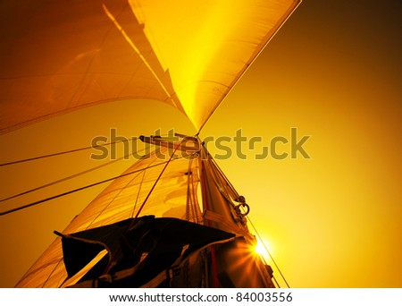 Sail over warm yellow sunset sky, sailboat over natural background