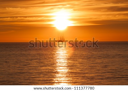 Sail ship silhouette at sea. Sun sunset on fire