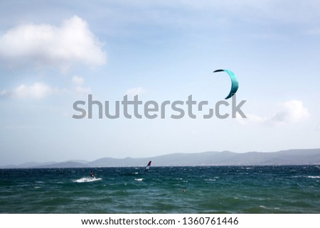 Sail surfing in sunny summer day. Adriatic Sea landscape with mountains island and sea waves.