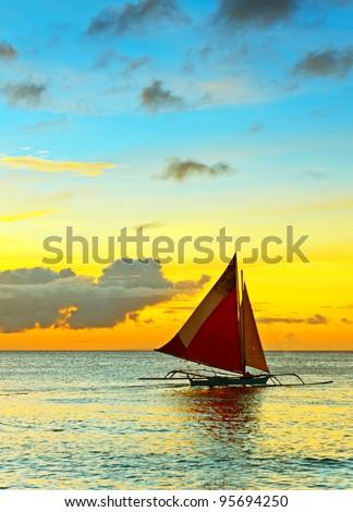 Sailboat against a orange sunset.