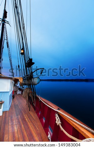 Sailboat anchored in still water at sea in the deep blue light of dawn. Copy space