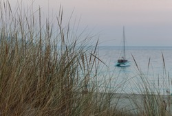 Sailboat anchored in the water close to the coat. Look through the sandy grass. Just after the sunset.