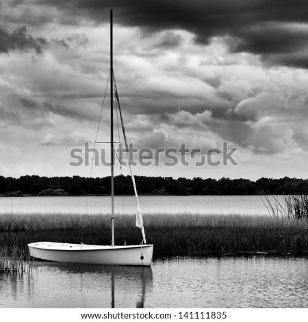 Sailboat anchored on lake during stormy day in monochrome image