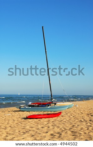 Sailboat and kayak on a deserted beach at Lake Michigan in the morning in summertime. - stock photo