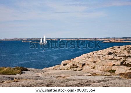 Sailboat and rocky coastline in sea archipelago