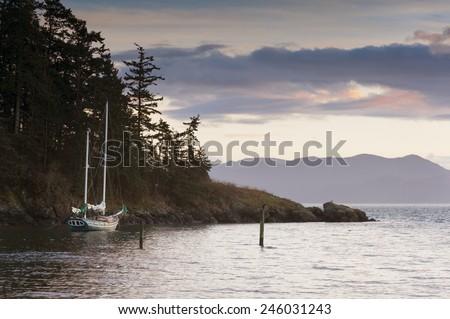 Sailboat at Sunset. A sailboat anchors off of Lummi Island in the San Juan Islands of Puget Sound, Washington state.
