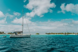 Sailboat at the sea, close to a tropical sandy island in Carriacou, the Caribbean Islands, white exotic sandy beach