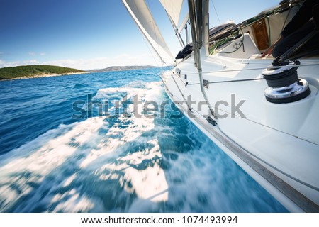Sailboat at windy day floats in clear water / sea