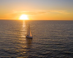 Sailboat entering Newport Beach Harbor at sunset off the coast of California