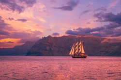 Sailboat in Santorini, Greece. Sailing ship navigate near an island in Cyclades. The photo is taken at sunset.