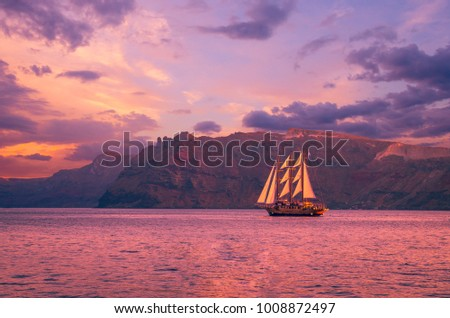 Sailboat in Santorini, Greece. Sailing ship navigate near an island in Cyclades. The photo is taken at sunset. #1008872497