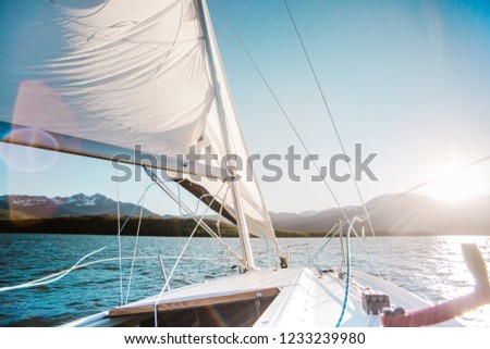 Sailboat in the mountain lake with the mountains on the background. White sail and sunset or sunrise.