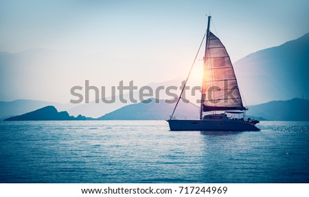 Stock Photo Sailboat in the sea in the evening sunlight over beautiful big mountains background, luxury summer adventure, active vacation in Mediterranean sea, Turkey