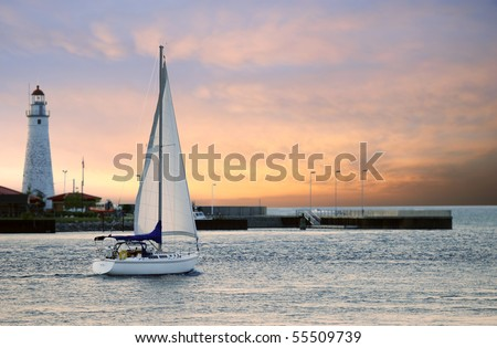 sailboat leaving marina - stock photo