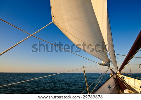 Sailboat navigating towards sunset in the caribbean.